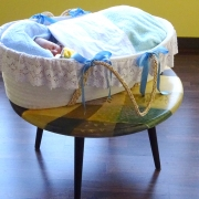 baby asleep in basket on coffee table